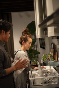 キッチンで一緒に家事をしているカップルの写真素材 [FYI03004175]