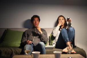 ポップコーンを食べながらテレビを見ているカップルの写真素材 [FYI03004179]
