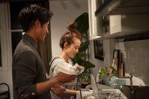 キッチンで一緒に家事をしているカップルの写真素材 [FYI03004182]