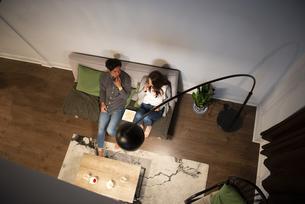 ポップコーンを食べながらテレビを見ているカップルの写真素材 [FYI03004184]