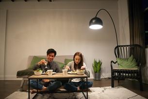 リビングで食事をしているカップルの写真素材 [FYI03004185]