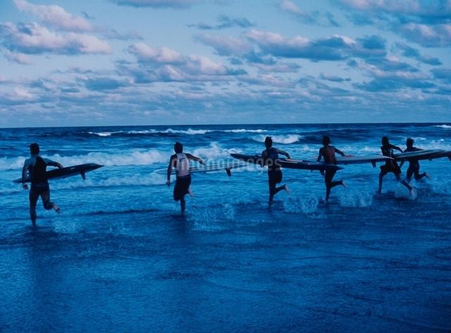 波に向かって走っているサーファー達(青)の写真素材 [FYI03004334]