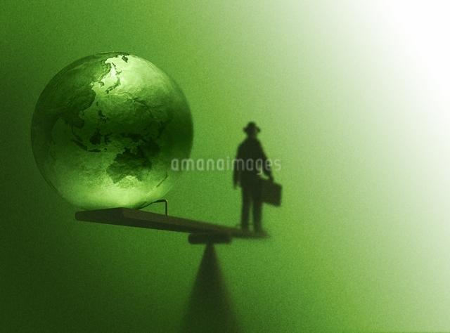 シーソーに乗るスーツ姿の男性と地球(黄緑色)の写真素材 [FYI03004451]