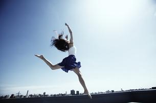 空高く飛ぶ若い女性の写真素材 [FYI03007542]