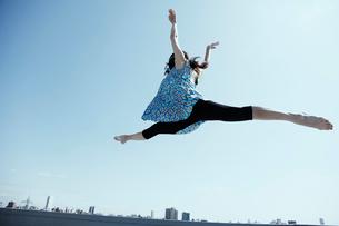 空高く飛ぶ若い女性の写真素材 [FYI03007543]
