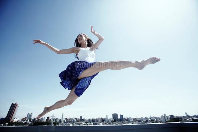 空高く飛ぶ若い女性の写真素材 [FYI03007544]