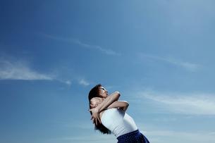 青い空と光を感じる女性の写真素材 [FYI03007551]
