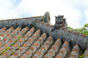 屋根に設置された魔除けのシーサー像の写真素材 [FYI03013637]