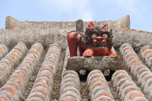 屋根に設置された魔除けのシーサー像の写真素材 [FYI03013639]
