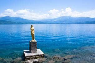 翡翠色に輝く夏の田沢湖とたつこ像の写真素材 [FYI03015880]