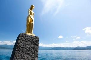 翡翠色に輝く夏の田沢湖とたつこ像の写真素材 [FYI03015882]