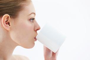 マグカップから飲み物を飲む白人女性の写真素材 [FYI03017663]