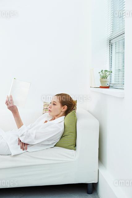 ソファで読書する白人女性の写真素材 [FYI03017694]