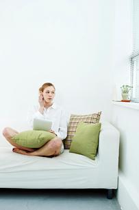 タブレットPCで音楽を聴く白人女性の写真素材 [FYI03017714]
