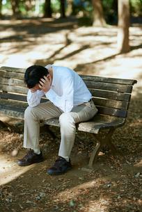 公園で項垂れる男性の写真素材 [FYI03018518]