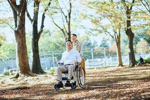 公園を車椅子で散歩する老夫婦の写真素材 [FYI03018539]