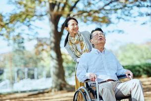 公園を車椅子で散歩する老夫婦の写真素材 [FYI03018544]