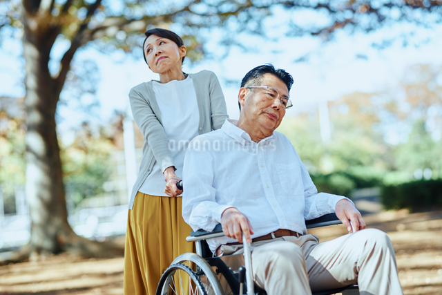 公園を車椅子で散歩する老夫婦の写真素材 [FYI03018549]