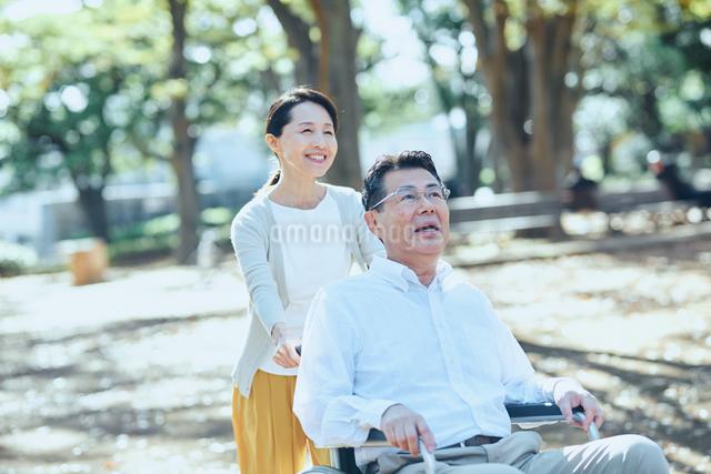 木漏れ日のさす公園で散歩する老夫婦の写真素材 [FYI03018556]