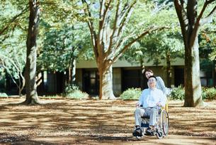 木漏れ日のさす公園で散歩する老夫婦の写真素材 [FYI03018563]