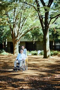 木漏れ日のさす公園で散歩する老夫婦の写真素材 [FYI03018564]