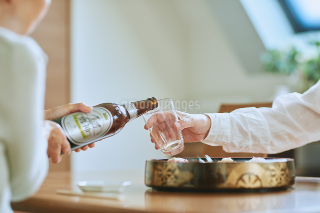 ビールをそそぐ妻とグラスを持つ夫の写真素材 [FYI03018626]