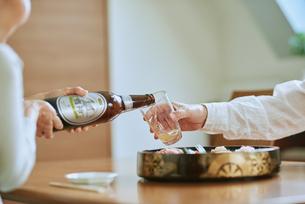 ビールをそそぐ妻とグラスを持つ夫の写真素材 [FYI03018628]
