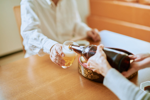 ビールをそそぐ妻とグラスを持つ夫の写真素材 [FYI03018638]