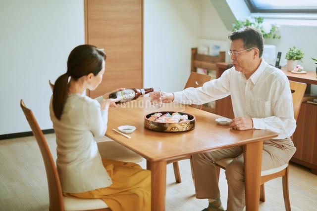 ビールをそそぐ妻とグラスを持つ夫の写真素材 [FYI03018640]