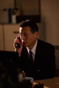 電話をする退職前の男性社員の写真素材 [FYI03018702]