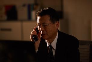 電話をする退職前の男性社員の写真素材 [FYI03018703]