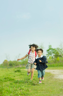 草原を走る姉弟の写真素材 [FYI03018738]