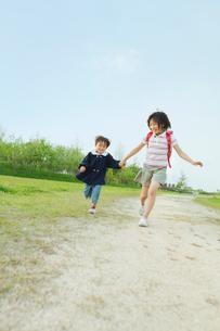 手を繋いで走る姉弟の写真素材 [FYI03018745]