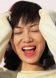 頭を抱える女性の写真素材 [FYI03025464]