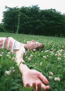 草原に寝転ぶ女性の写真素材 [FYI03027565]