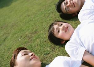 芝生に寝転ぶ親子の写真素材 [FYI03029483]