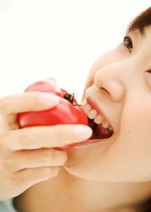 トマトを食べる女性の写真素材 [FYI03030126]