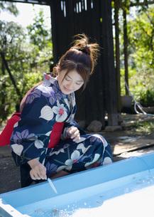 金魚すくいをする浴衣姿の女性の写真素材 [FYI03030291]