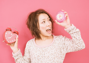 目覚まし時計を持つ女性の写真素材 [FYI03035663]