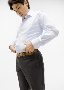 腹部をつまむ男性の写真素材 [FYI03037620]