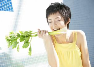 セロリを食べる女性の写真素材 [FYI03037703]