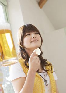 ポテトチップスを食べる女性の写真素材 [FYI03038026]