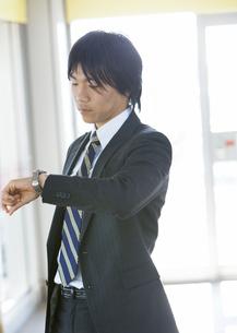 腕時計を見るビジネスマンの写真素材 [FYI03038313]