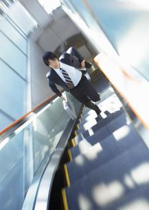 エスカレーターを駆け上がるビジネスマンの写真素材 [FYI03038316]