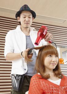 髪をブローする美容師の写真素材 [FYI03038888]