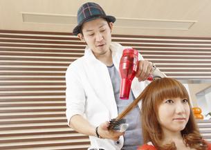髪をブローする美容師の写真素材 [FYI03038889]