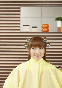 髪にロットを巻いた若い女性の写真素材 [FYI03038891]