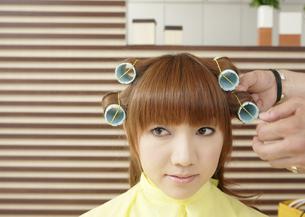 髪にロットを巻かれる若い女性の写真素材 [FYI03038892]