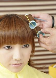 髪にロットを巻かれる若い女性の写真素材 [FYI03038894]