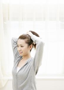 髪を束ねる若い女性の写真素材 [FYI03039012]